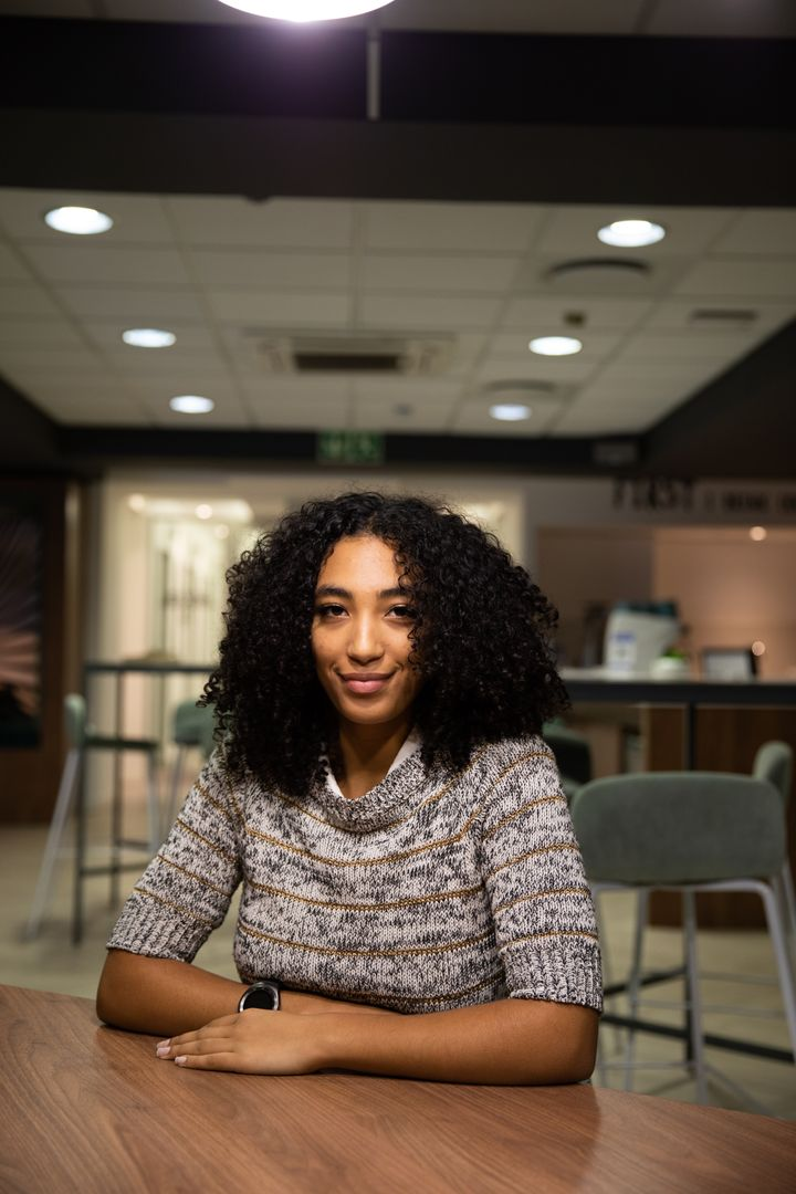 Portrait of a mixed race professional woman working late in a modern office, sitting by a desk, looking at the camera and smiling Free Stock Images from PikWizard