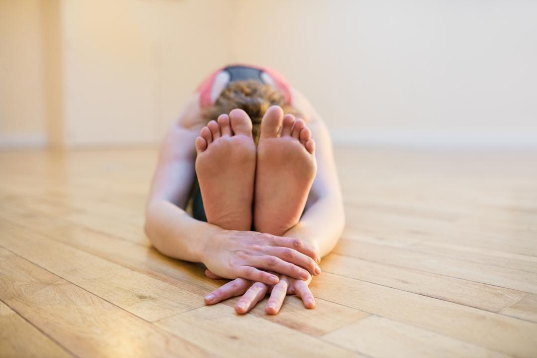 Woman performing paschimottanasana pose in fitness gym