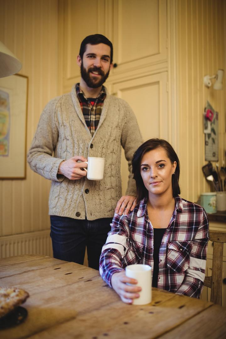 Couple holding mug of coffee at home