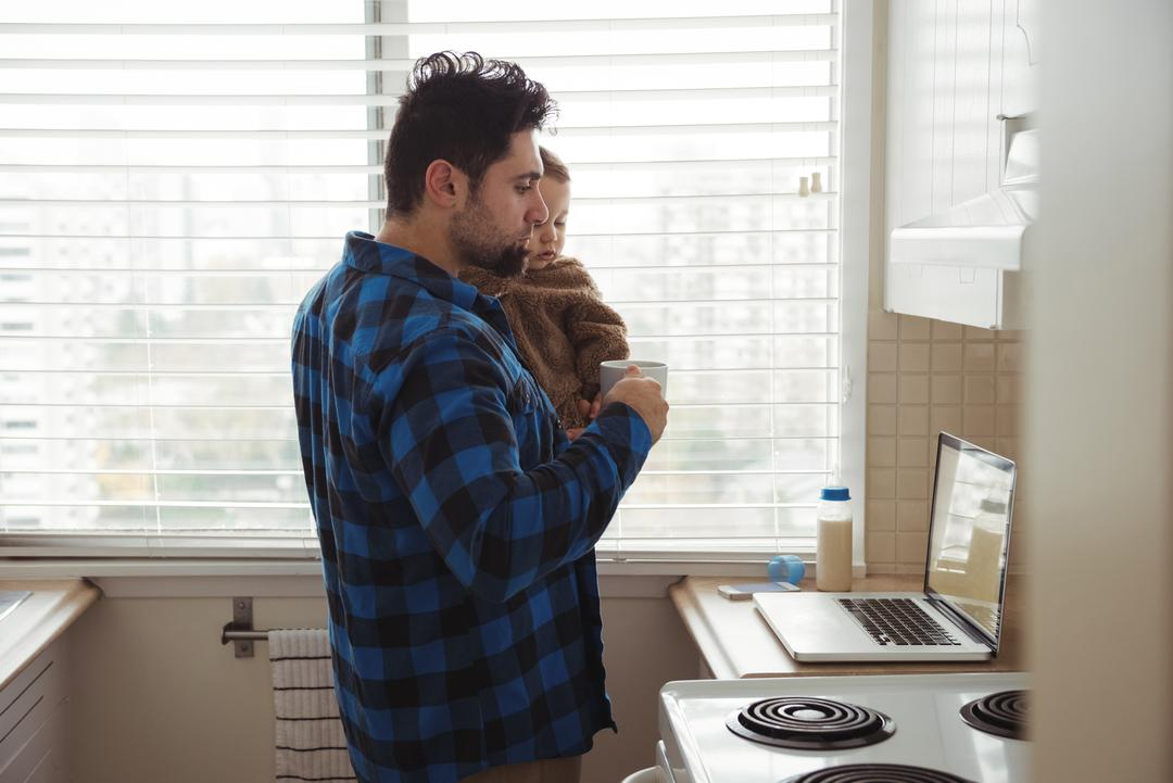 Father having coffee while holding his baby in kitchen