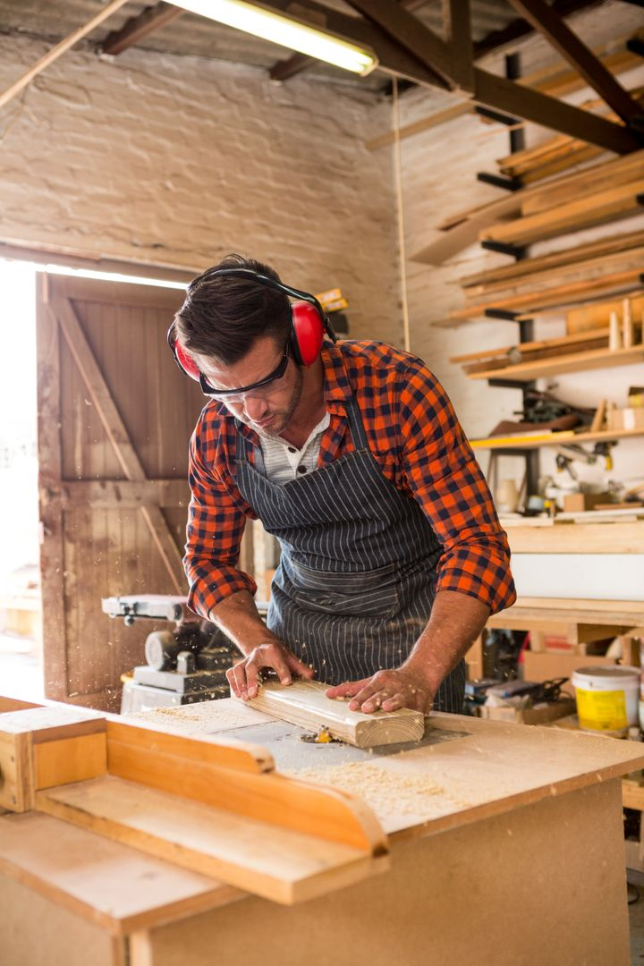Carpenter working on his craft in a dusty workshop Free Stock Images from PikWizard