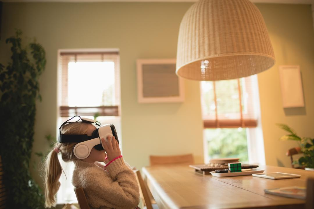 Girl sitting at table and using virtual realty headset at home