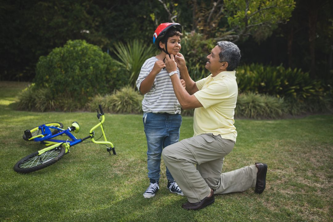 Grandfather helping grandson for wearing bicycle helmet at park Free Stock Images from PikWizard