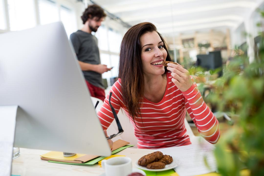 Female graphic designer having a cookie in office