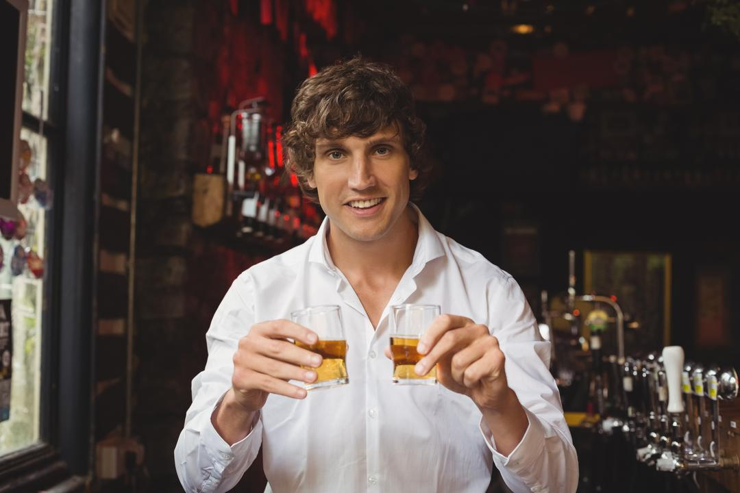 Portrait of bartender holding whisky shot glasses at bar counter in bar