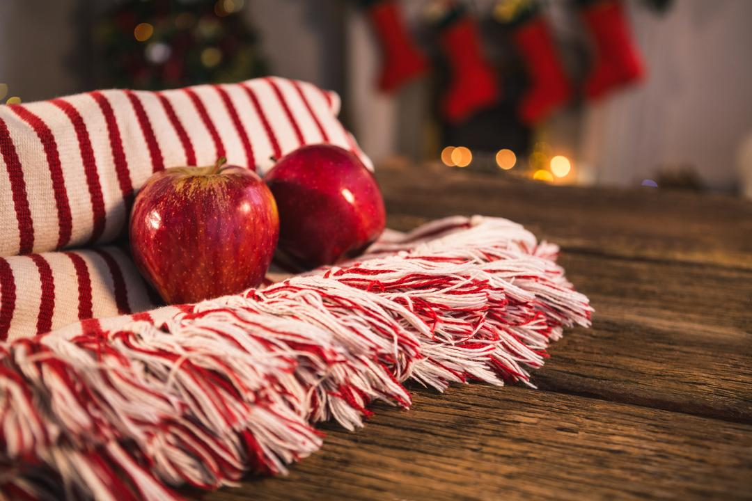 Rolled blanket with two apples on wooden table against christmas decor Free Stock Images from PikWizard