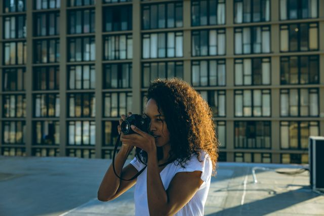 Young mixed race woman taking photos on urban rooftop