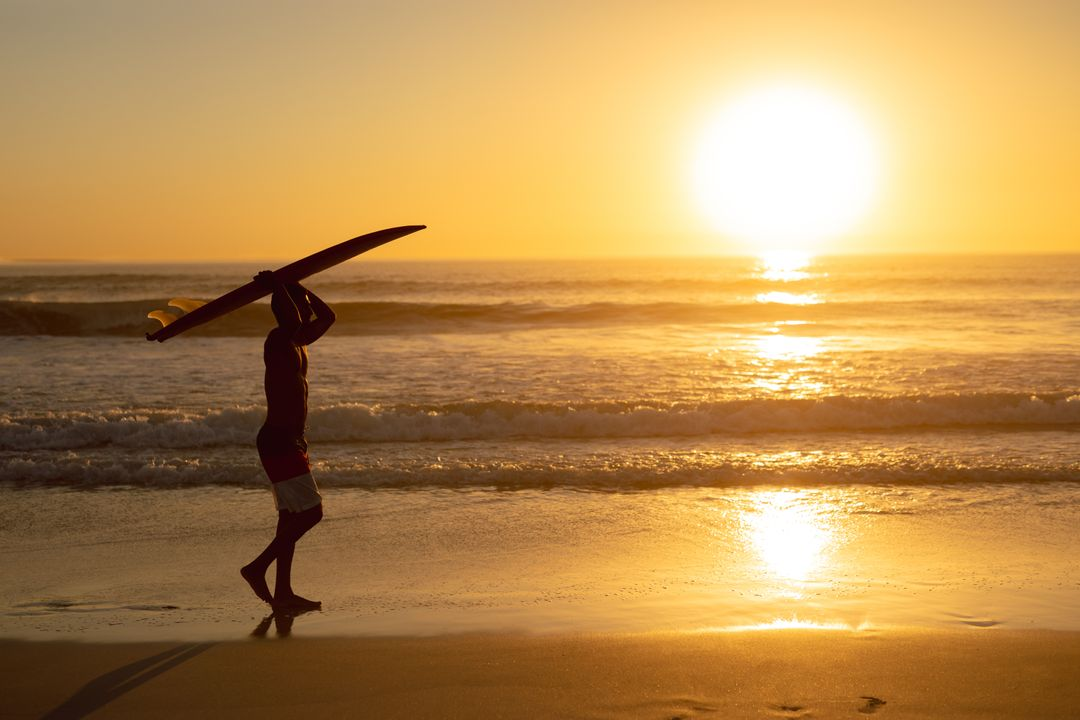 Man walking with surfboard on his head at beach during sunset