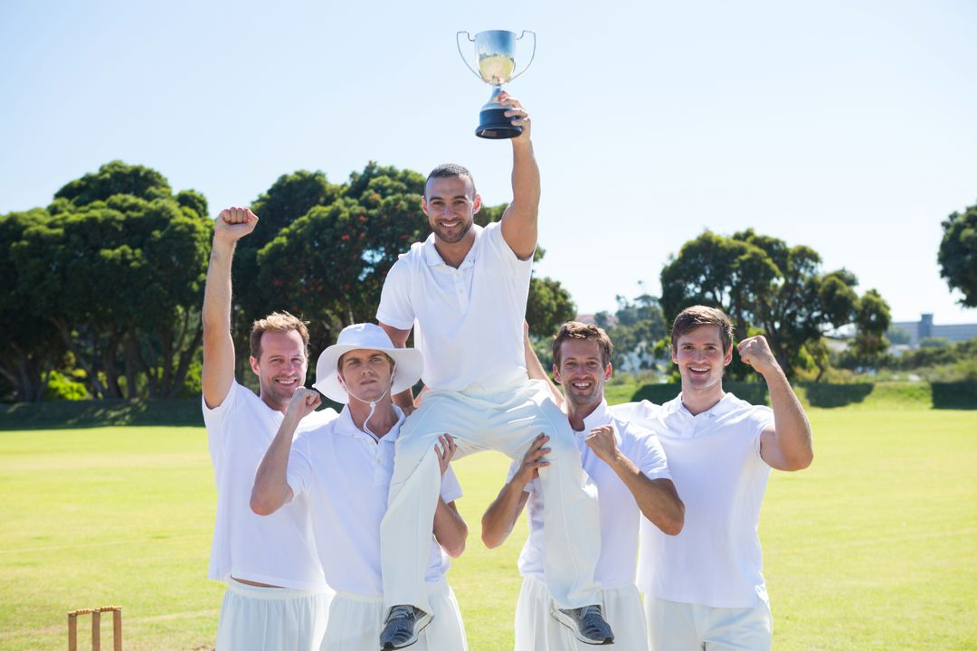 Happy cricket team with throphy standing on field against clear sky
