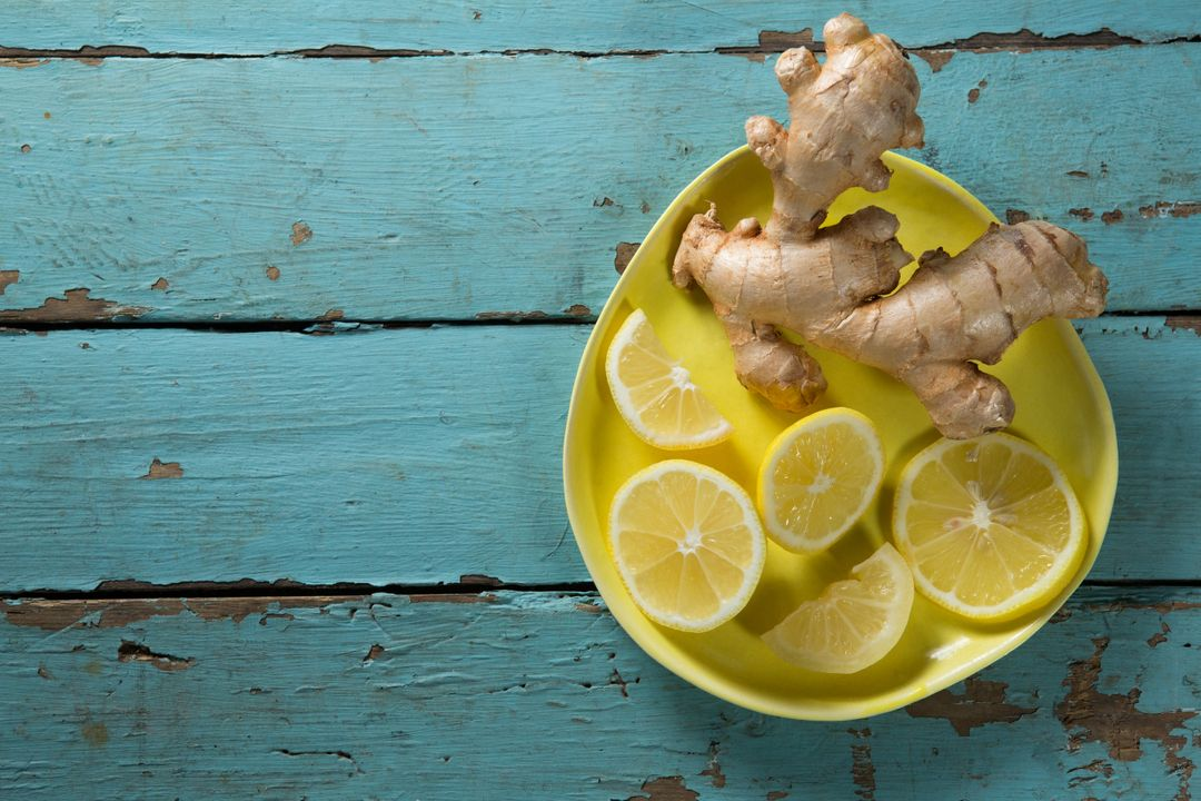 Overhead view of lemon and ginger in plate on textured wooden table Free Stock Images from PikWizard