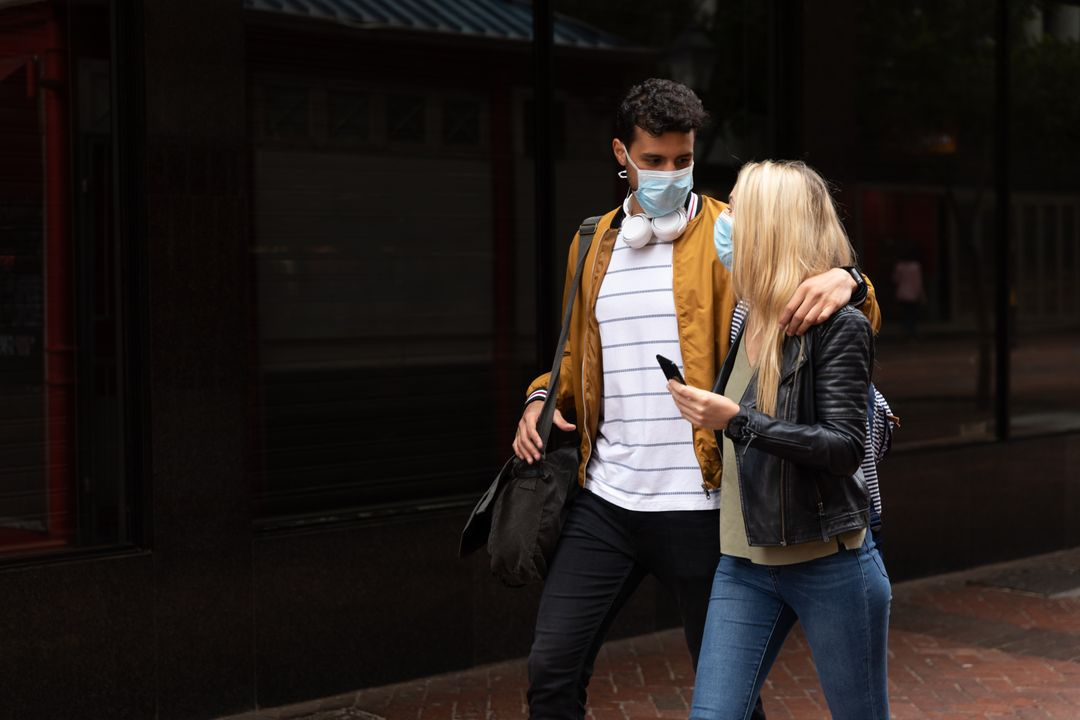 Caucasian couple out and about in the city streets during the day, wearing face masks against air pollution and covid19 coronavirus, embracing and talking while they walk, woman holding a smartphone. Free Stock Images from PikWizard
