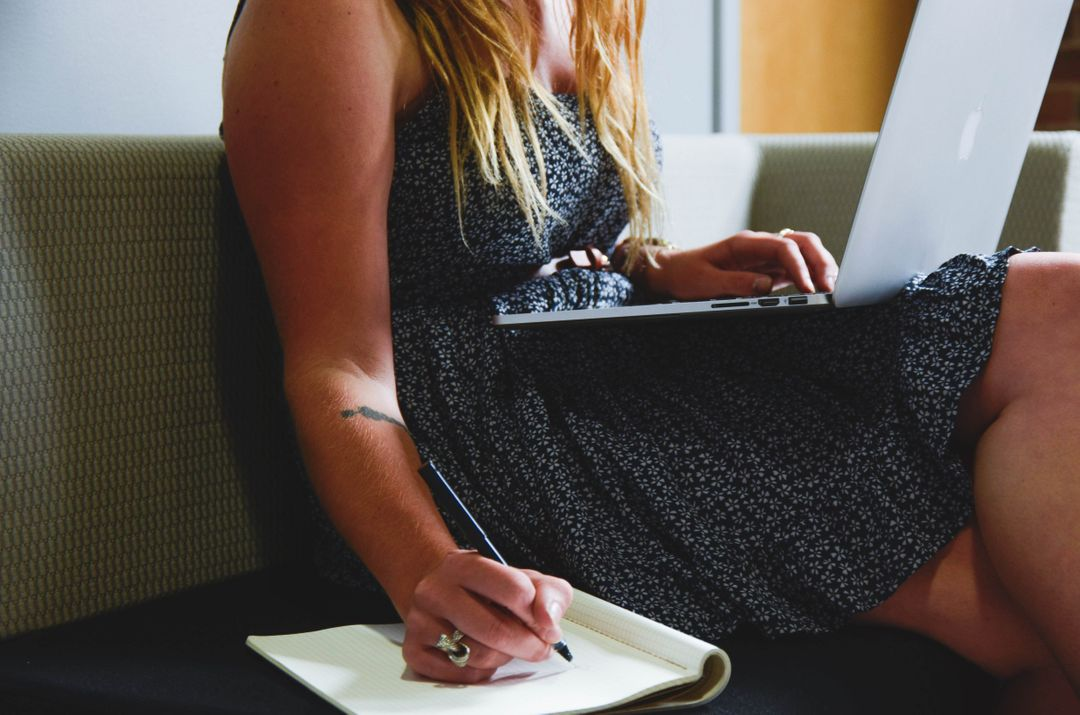 low image of a woman sitting while writing notes and laptop on her lap