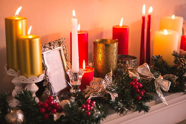 Candles and christmas decorations arranged on fireplace at home