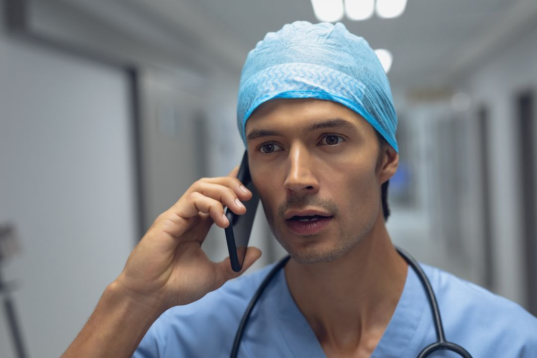 Male surgeon talking on mobile phone in the corridor at hospital