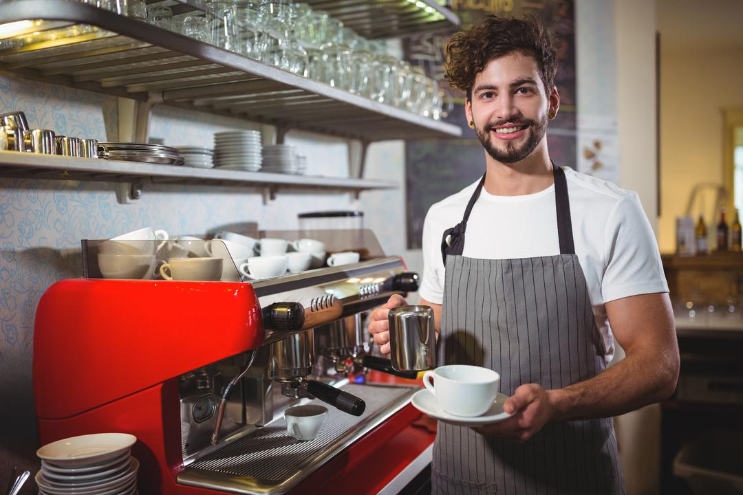 Portrait of smiling waiter making cup of coffee at counter in cafe
