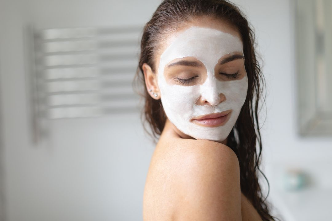 Beautiful woman with facial mask ad eye closed standing in bathroom at home