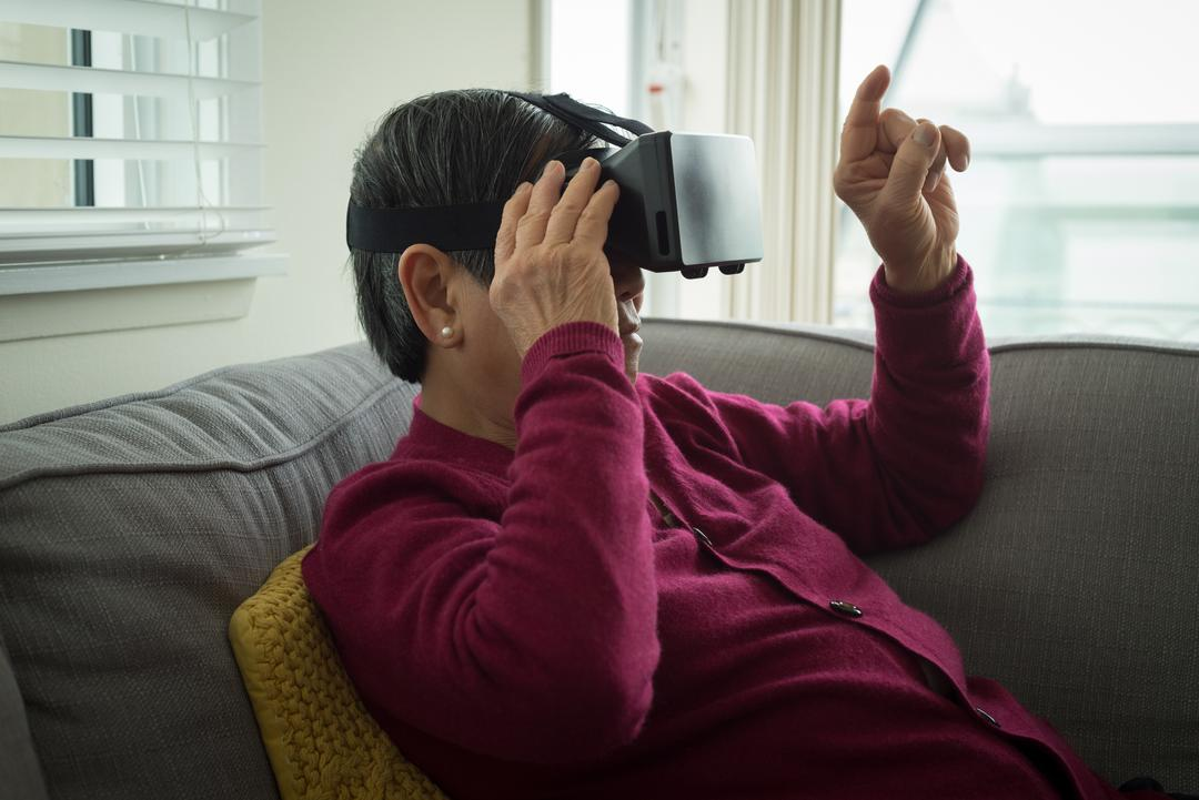 Senior woman using vr glasses while sitting on sofa at home