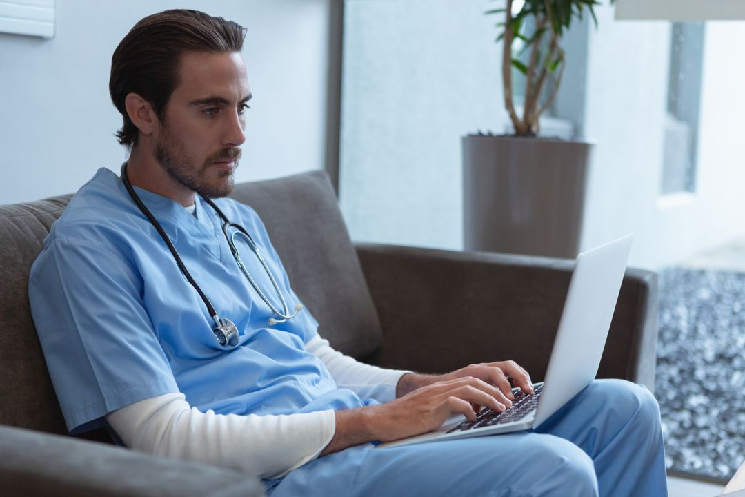 Male surgeon using laptop on sofa in lobby at hospital