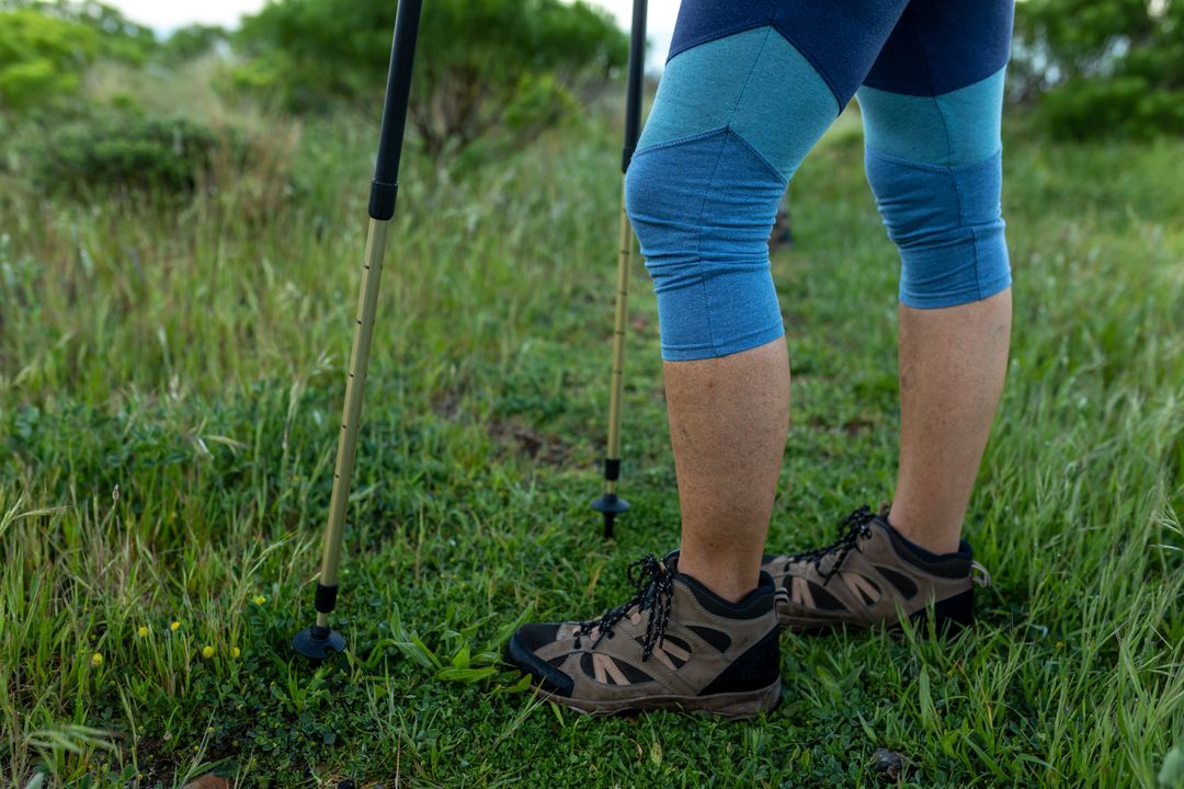 Low section of caucasian hiker senior woman with hiking poles trekking in the mountains. Trekking hiking and adventure concept. Free Stock Images from PikWizard