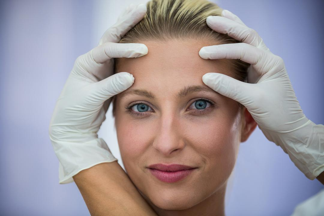 Doctor examining female patients face from cosmetic treatment Free Stock Images from PikWizard