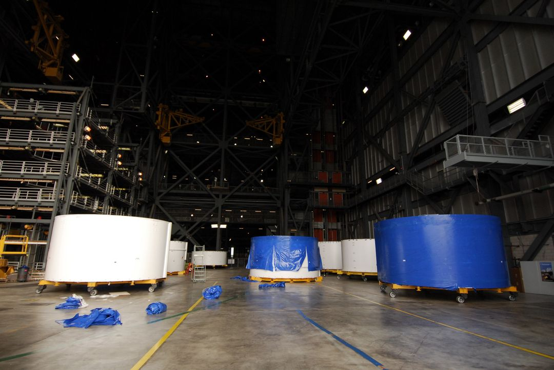 CAPE CANAVERAL, Fla. –  Inside the Vehicle Assembly Building high bay 4 at NASA's Kennedy Space Center in Florida, Ares I-X upper stage simulator segments are lined up.  Their protective blue shrink-wrapped covers used for shipping are being removed, as seen on the segments at left and in the back. The upper stage simulator will be used in the test flight identified as Ares I-X in 2009.  The segments will simulate the mass and the outer mold line and will be more than 100 feet of the total vehicle height of 327 feet.  The simulator comprises 11 segments that are approximately 18 feet in diameter.  Most of the segments will be approximately 10 feet high, ranging in weight from 18,000 to 60,000 pounds, for a total of approximately 450,000 pounds. Photo credit: NASA/Troy Cryder