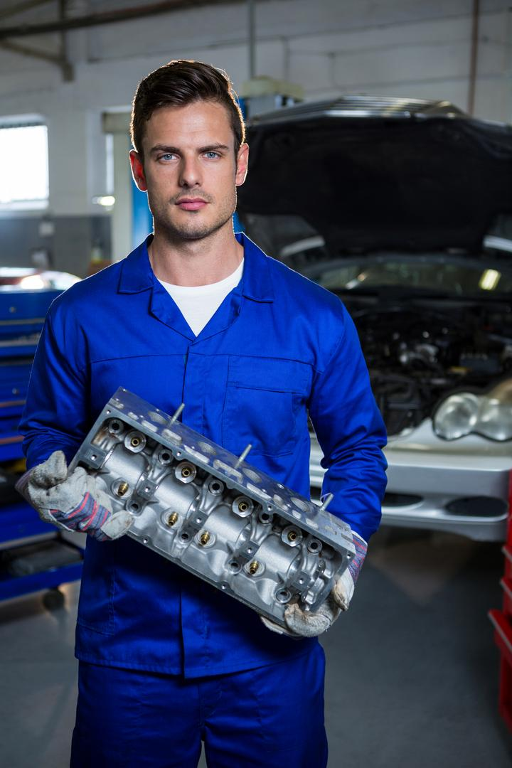 Portrait of serious mechanic holding car engine at repair garage