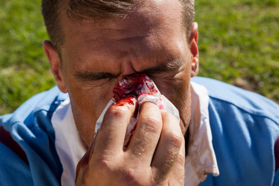 High angle view of rugby player with injured nose at playing field Free Stock Images from PikWizard