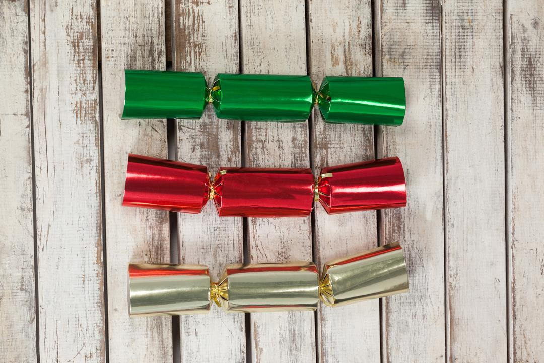 Red, green and golden Christmas crackers on wooden table