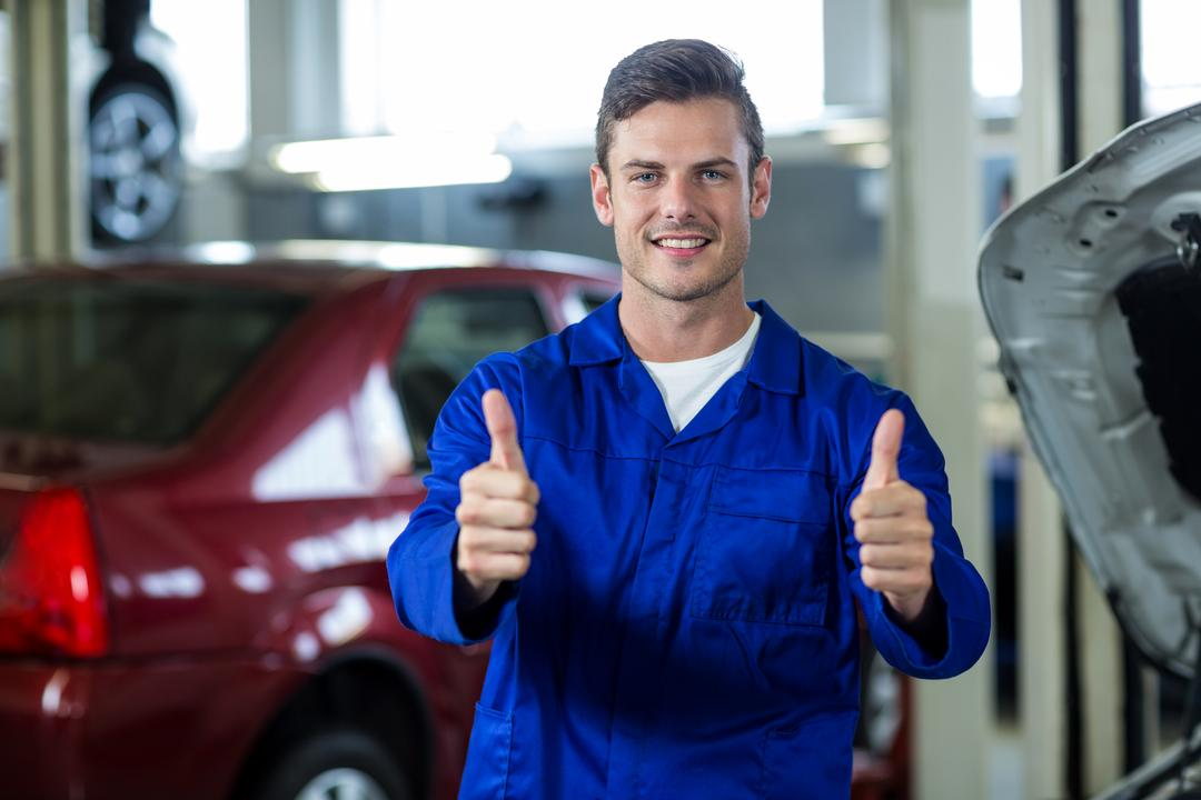Portrait of smiling mechanic standing in repair shop showing thumbs up Free Stock Images from PikWizard