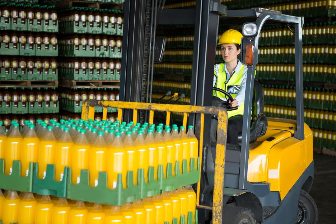 Confident female worker driving forklift in distribution warehouse