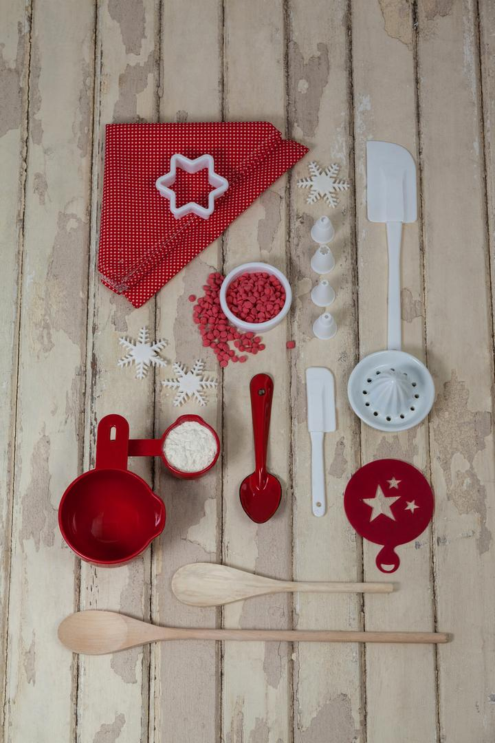 Spatula, spoons, icing sugar, dessert toppings and cookie cutter on wooden board