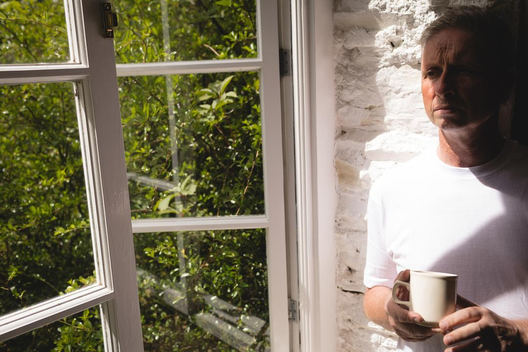 Thoughtful senior man having coffee near window at home Free Stock Images from PikWizard