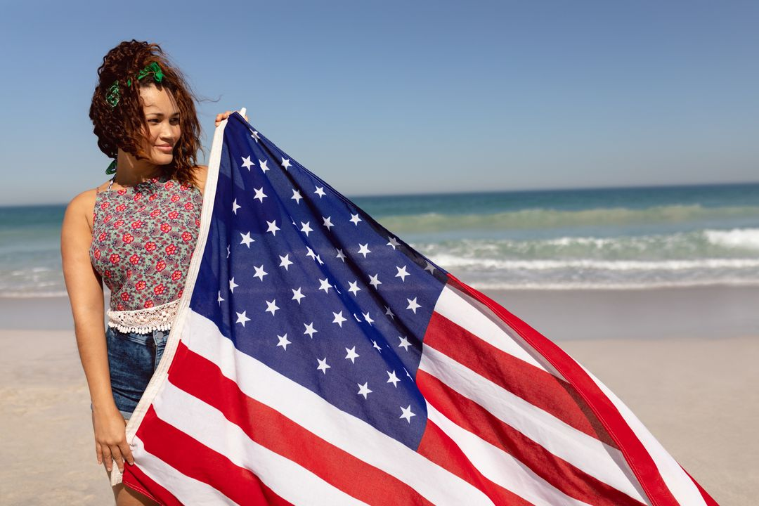 Front view of beautiful young Mixed-race woman holding american flag on beach in the sunshine