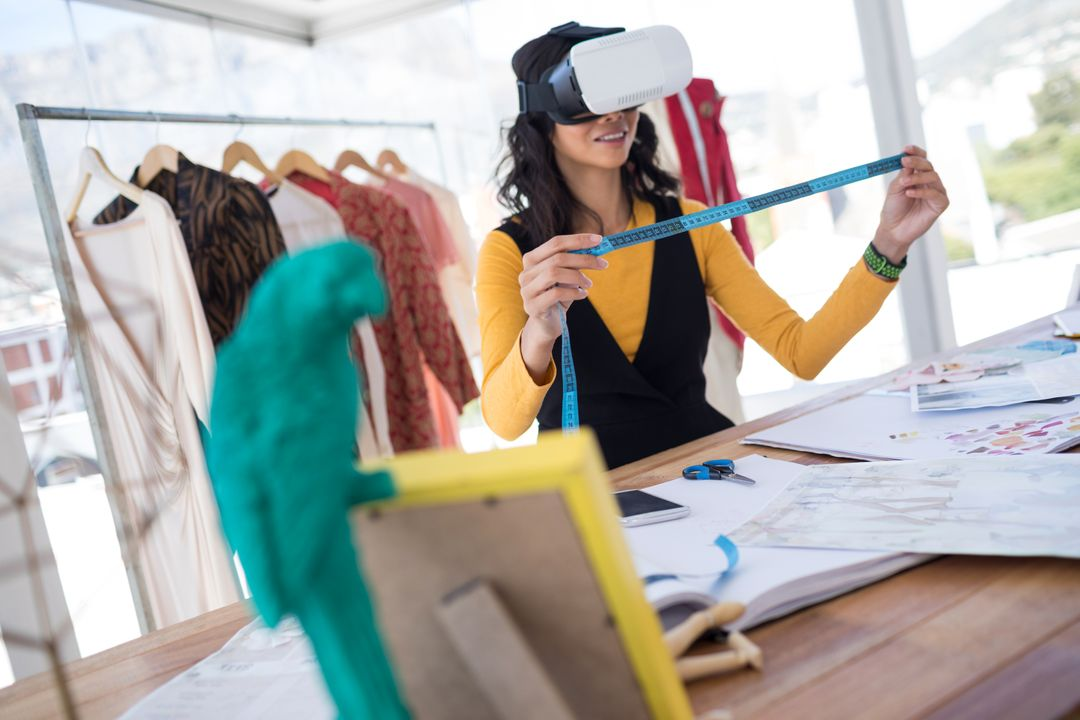 Female designer using virtual reality headset in office