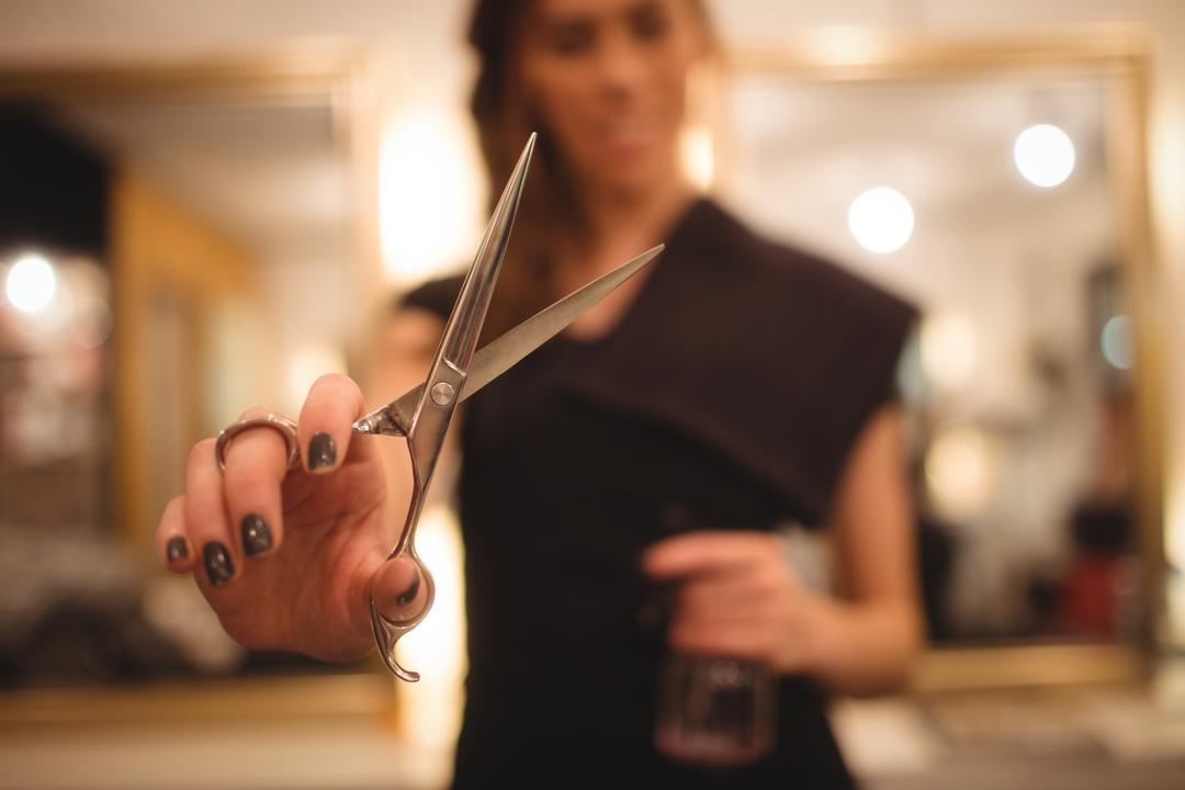 Female hairdresser holding scissor at saloon