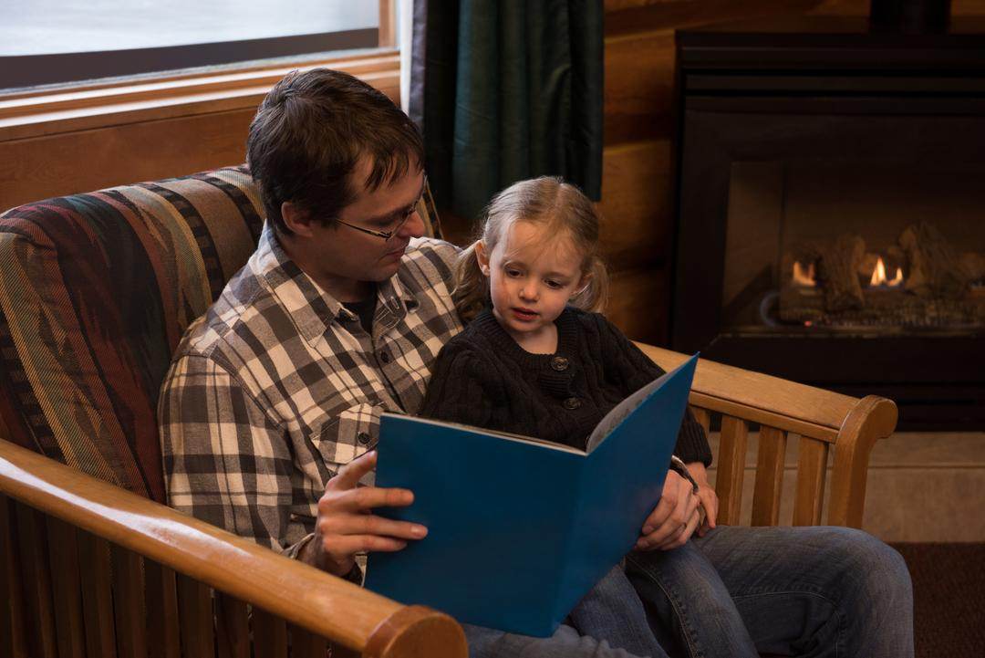 Father reading story book to daughter on chair at home