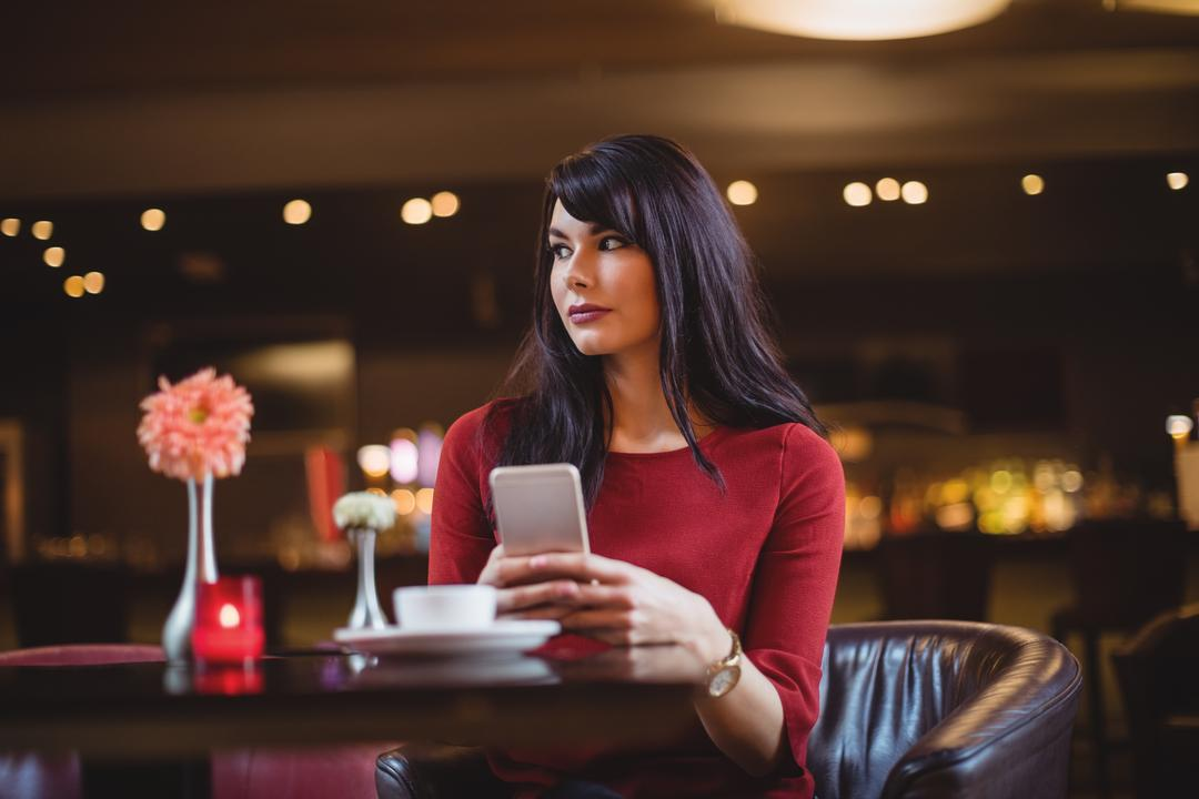Woman holding mobile phone in restaurant