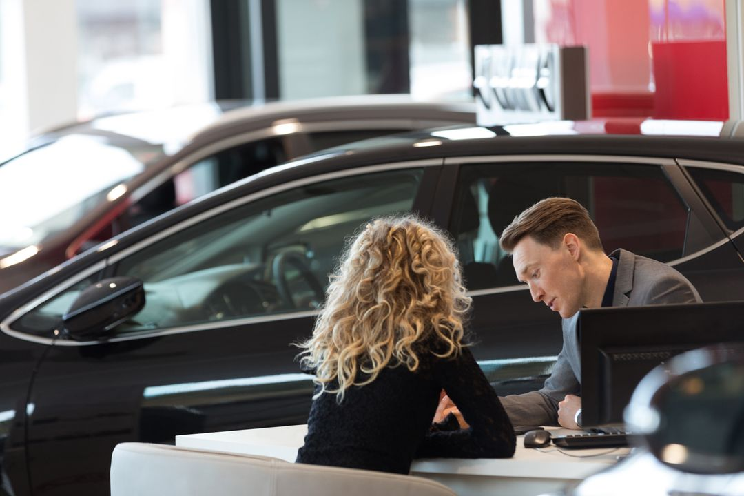 Car salesperson discussing with female customer while sitting in showroom Free Stock Images from PikWizard