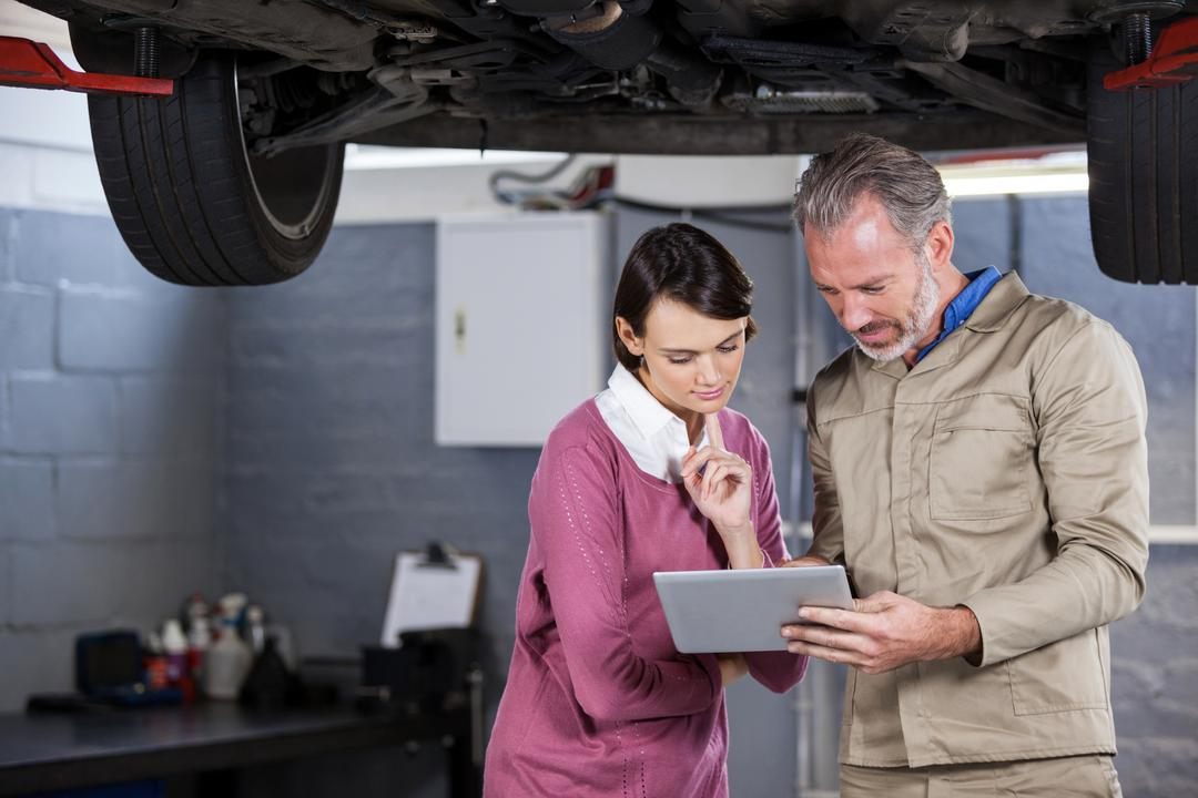 Mechanic explaining quotation to a customer on digital tablet at repair garage Free Stock Images from PikWizard
