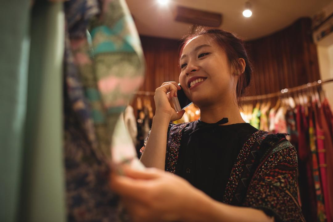 Woman talking on mobile phone while selecting a clothes on hanger at apparel store