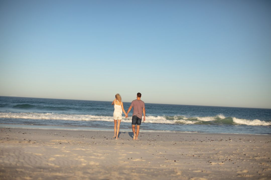 Rear view of couple walking hand in hand on the beach