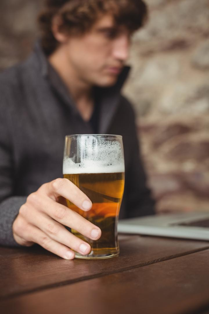 Man having beer while using laptop at bar Free Stock Images from PikWizard