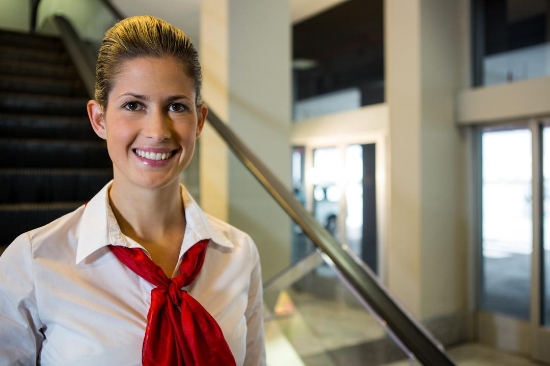 Portrait of smiling female staff standing on escalator in airport Free Stock Images from PikWizard