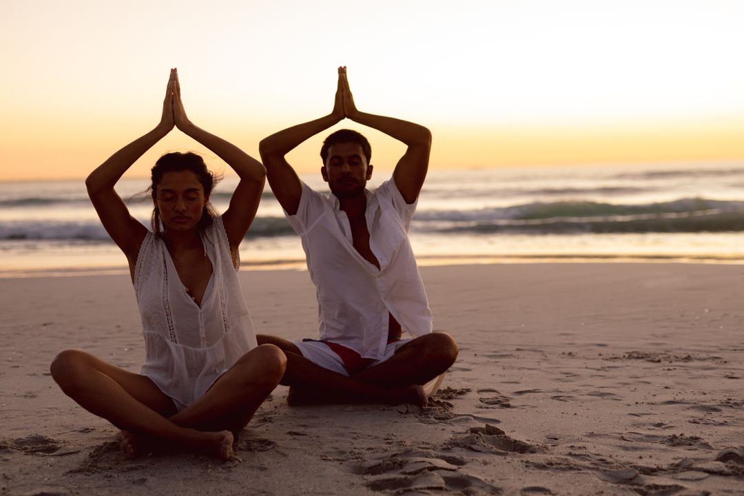 Couple performing yoga together on the beach during sunset Free Stock Images from PikWizard