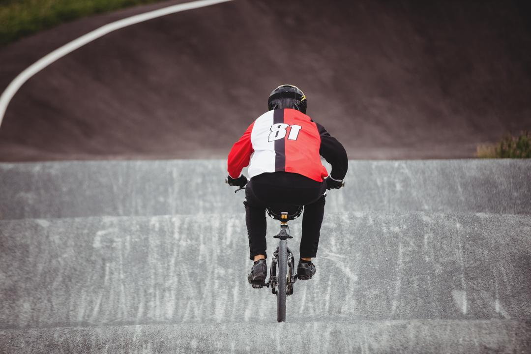 Rear view of cyclist riding BMX bike in skatepark