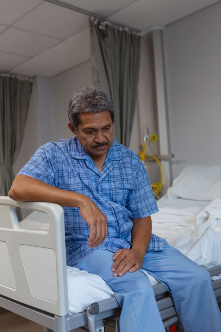 Front view of sad mature male patient sitting on bed in medical ward at hospital