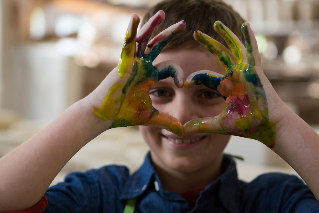 Boy gesturing with painted hands at pottery workshop Free Stock Images from PikWizard