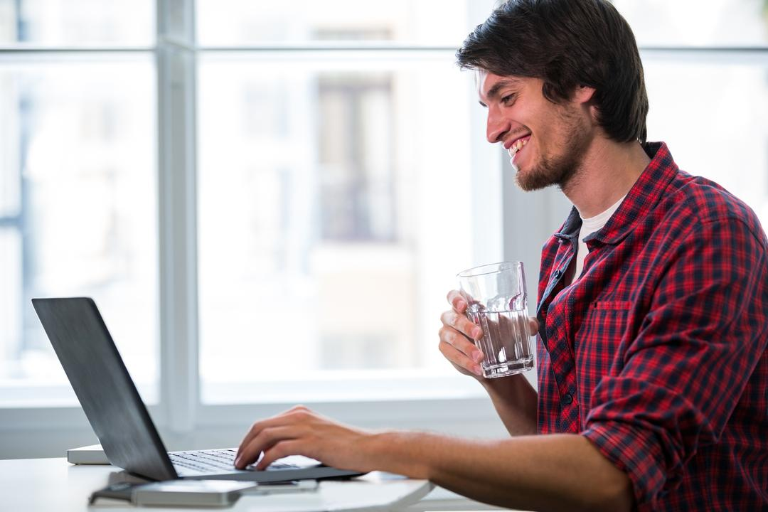 Male business executive having a glass of water while using laptop in office