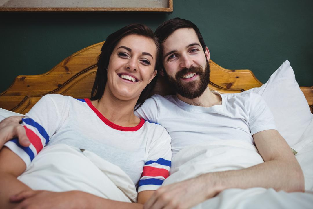 Portrait of couple lying together on bed at bedroom Free Stock Images from PikWizard