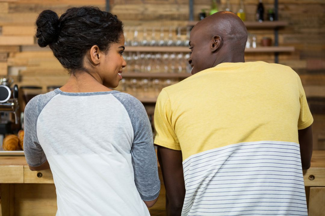 Rear view of young couple looking at each other in coffee shop